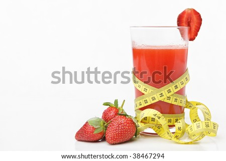 Strawberries and a glass of juice with measuring tape for diet and healthy life concept with lots of copy space