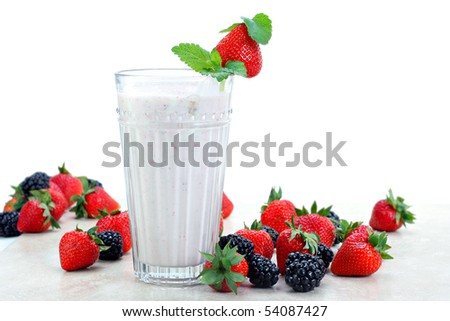Strawberries and blackberries surround a fresh berry smoothie drink.  White background for copy space. - stock photo
