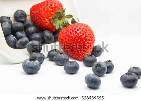Strawberries and blueberries on white background.
