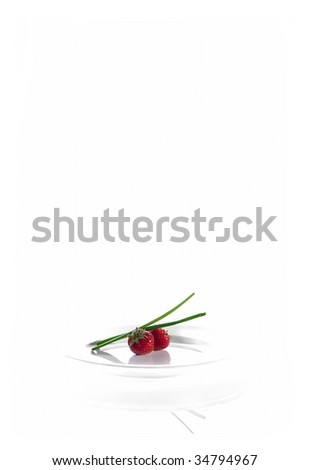 Strawberries and chives on a white plate