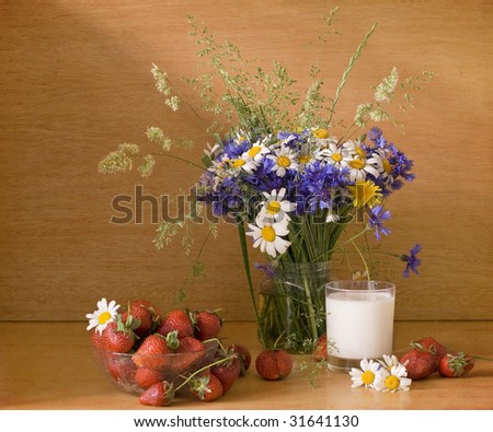 Strawberries and milk with wild flowers - stock photo