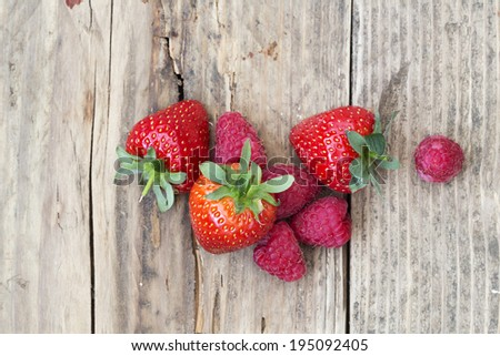 strawberries  and raspberrie summer fruits overhead shot on wooden background - stock photo