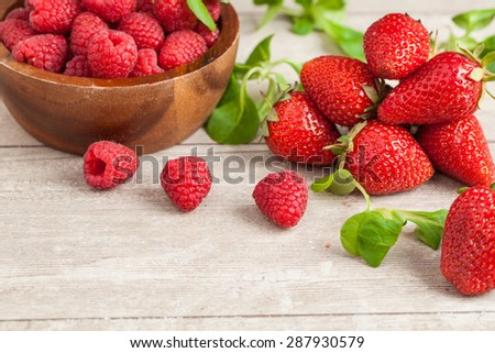 strawberries and raspberries in bowls, top view, close-up Selective focus - stock photo