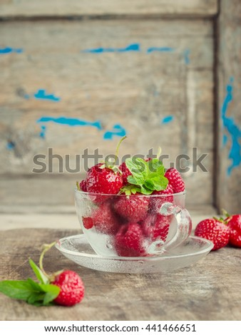 strawberries and raspberries with mint in glass Cup on wooden rustic background. toned image - stock photo