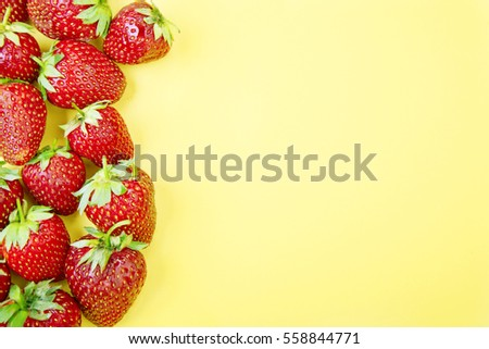 Strawberries arranged group on a yellow background