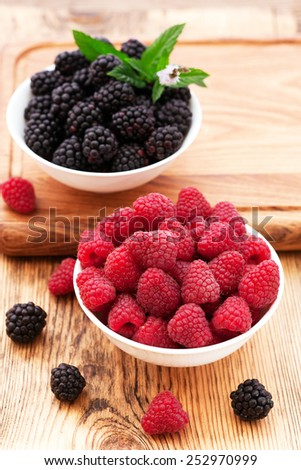strawberries, blueberries, blackberries and raspberries in bowls, top view, close-up. Selective focus. - stock photo