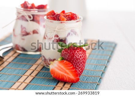 Strawberries desert with cream served on glass cups over table top. - stock photo