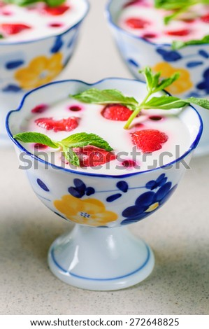Strawberries desert with cream served on ice cream bowls over table top - stock photo