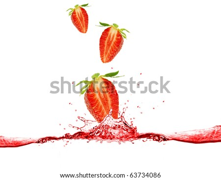 Strawberries falling into juice - stock photo