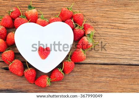 Strawberries  heart shape in heart shape bowl - stock photo