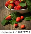 Strawberries in a basket in the garden - stock photo