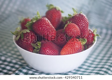 strawberries in a bowl in the daylight