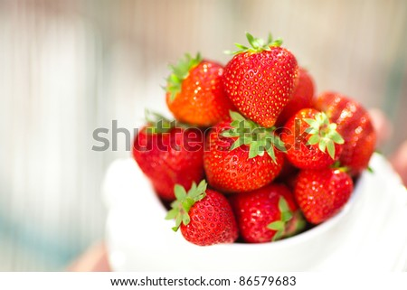 strawberries in a bowl in the daylight - stock photo