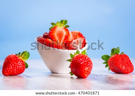 Strawberries in a bowl on wooden table