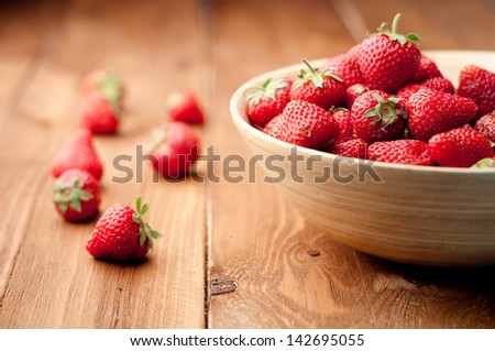 Strawberries in a Bowl, ona a wooden background - stock photo