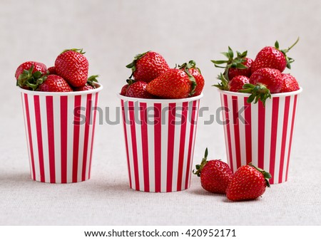 Strawberries in a striped cups. Selective focus. - stock photo