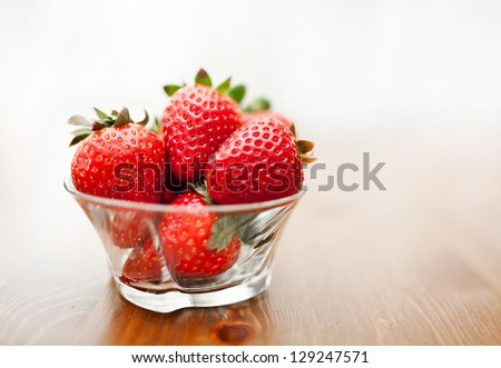 Strawberries in glass bowl - stock photo