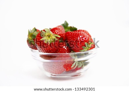 Strawberries in glass bowl isolated on white background