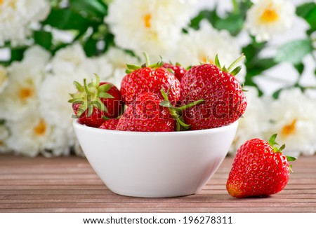 Strawberries in the white bowl on the flower background. - stock photo
