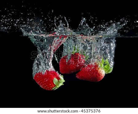 strawberries in water with bubbles on black ground - stock photo
