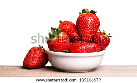 Strawberries in white plate on the wooden board. Isolated on white. - stock photo