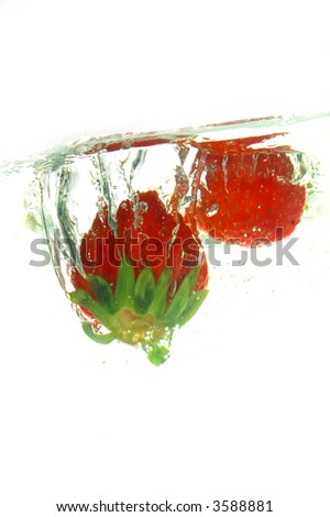 Strawberries jumping into water - stock photo