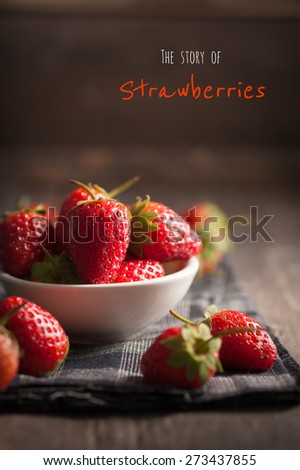 Strawberries on wood background with written words in vintage style with low key scene. - stock photo