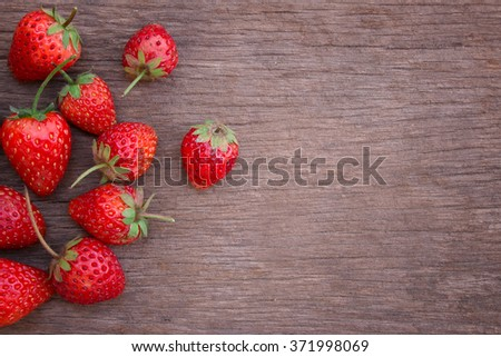 Strawberries on wood background with written words in vintage style with selective focus . background for text / strawberry background. - stock photo