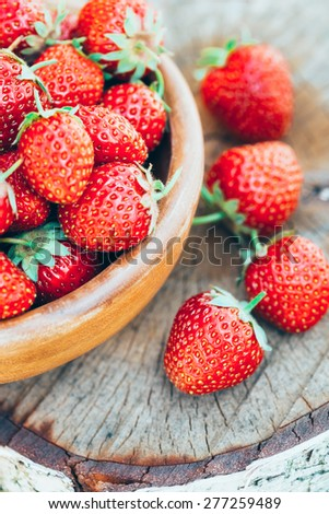 Strawberries. Organic Berries Closeup. Ripe Strawberry In The Fruit Garden, Old Wooden Bowl Filled With Succulent Juicy Fresh Ripe Red Strawberries On Old Birch Stump - stock photo