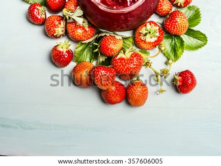 Strawberries preserve with fresh berries and jam-jar on  light wooden background, top view - stock photo