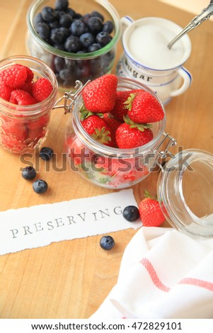 Strawberries, raspberries and blueberries in glass jars with the word preserving on cutting board