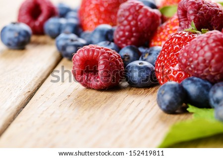 Strawberries raspberries and blueberries on the wooden table macro