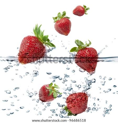 strawberries splash in transparent water, on white background - stock photo