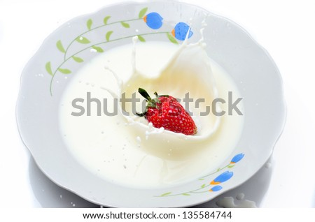Strawberries splashing in to milk on white plate isolated on white background
