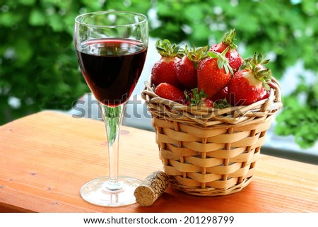 strawberries with a glass of red wine outdoors - stock photo