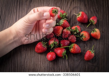 strawberries with hand pick up on wooden background - stock photo