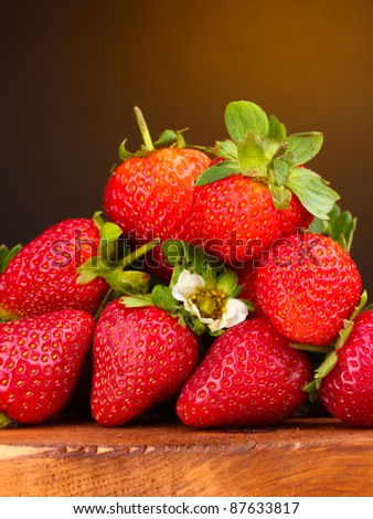 Strawberries with leaves on wooden table on brown  background - stock photo