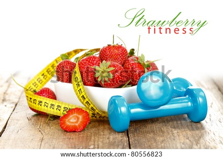 Strawberries with measure tape and weights, healthy life concept with place for your text on the right