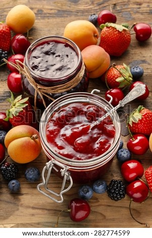Strawberry and blueberry jams in glass jars - stock photo