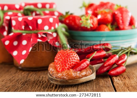 Strawberry and chilli jam on a rustic wooden table - stock photo