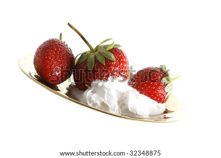 strawberry and cream close-up in a golden plate isolated on white