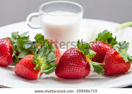 strawberry and glass of milk on white plate - stock photo