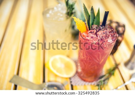 strawberry and pineapple alcoholic beverage, served cold with ice at bar. Cocktail drinks with lime, pineapple and alcohol as refreshment drinks on a summer day - stock photo