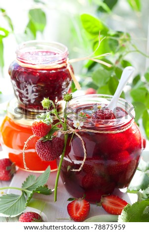 strawberry,apricot, raspberry jam in a jars and fresh berries - stock photo