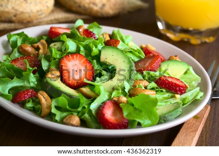 Strawberry, avocado, lettuce salad with cashew nuts on plate, photographed on dark wood with natural light (Selective Focus, Focus one third into the salad)
