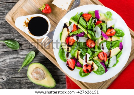 strawberry, baby spinach, red onion goat cheese and avocado salad on a white dish on a cutting board with caramelized balsamic vinegar in a gravy boat, top view - stock photo