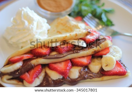 Strawberry Banana Nutella Crepe with Whipped Cream - stock photo