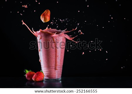 Strawberry banana smoothie with splash and copy space - stock photo