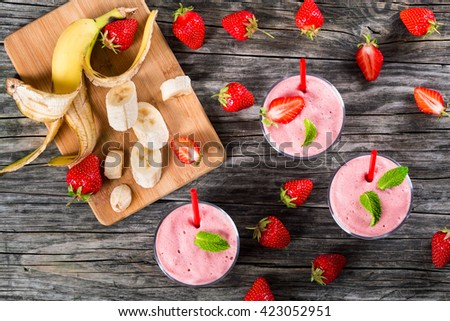 Strawberry Banana Smoothies Cups , slices of banana on a cutting board on an old rustic wooden table, studio lights, view from above - stock photo
