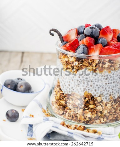 Strawberry, blueberries, oatmeal and chia seeds pudding in a jar for breakfast - stock photo
